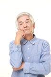 Senior Japanese man worries about something. Studio shot of senior Japanese man on white background Stock Photography