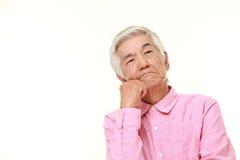 Senior Japanese man worries about something. Studio shot of senior Japanese man on white background Stock Image