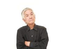 Senior Japanese man worries about something. Studio shot of senior Japanese man on white background royalty free stock photos