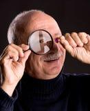 Senior jeweler looking at jewelry through magnifying glass Stock Photos
