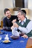 Senior Jewish man, adult son celebrating Hanukkah. Senior Jewish man and adult son celebrating Hanukkah