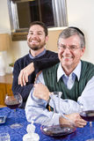 Senior Jewish man, adult son celebrating Hanukkah Royalty Free Stock Images
