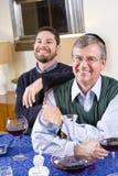 Senior Jewish man, adult son celebrating Hanukkah royalty free stock images