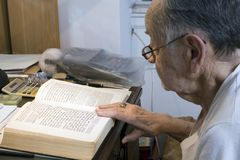 Senior with Jewish Prayer Book. A senior Romanian Jewish man reads from his Jewish Prayer Book.  He was 91 years old at the time  of shoot and was photographed Royalty Free Stock Photography
