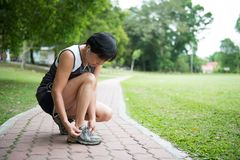 Senior jogger tighten her running shoe laces. Senior woman jogger tighten her running shoe laces Royalty Free Stock Images