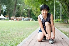 Senior jogger tighten her running shoe laces. Senior woman jogger tighten her running shoe laces Stock Photography