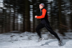 Senior jogging in the winter. A senior is jogging in the snow stock images