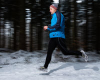 Senior jogging in the winter. A senior is jogging in the snow stock image