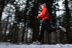 Senior jogging in the winter. A senior is jogging in the snow stock photo