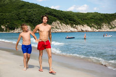 Senior and junior brothers walk along the beach. Royalty Free Stock Photo