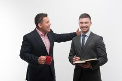 Senior and junior business people discuss. Something, boss with red cup patting shoulder of young employee, isolated on white background royalty free stock image