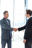 Senior and junior businessman shaking hands Stock Photography