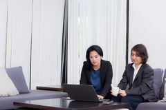 Senior and junior businesswoman discuss something during. Senior and junior businesswoman discuss something during their meeting Stock Photo