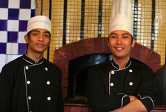 Senior and junior chef. In pose at work stock images