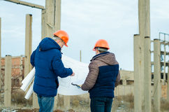Senior and junior engineers discussing work together. In construction Stock Photo