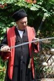 Senior Kuban Cossack checks blade of saber Royalty Free Stock Image