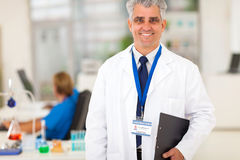 Senior lab researcher. Smiling senior lab researcher holding a clipboard Royalty Free Stock Image