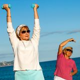 Senior ladies doing fitness exercises on beach. Stock Photography