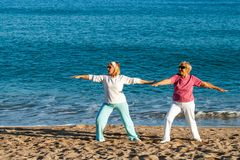 Senior ladies doing yoga on beach. Stock Photos