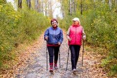 Senior ladies nordic walking. A portrait of two senior women nordic walking in a park stock images