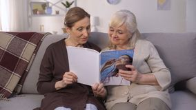 Senior ladies reading modern magazine with delight, many interesting information