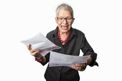 Senior lady angry with her bills. Elderly woman outraged with the bills she received, white background royalty free stock photography