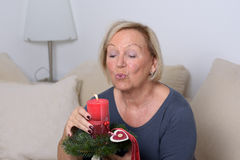 Senior lady blowing out a festive red candle Royalty Free Stock Image