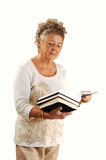 Senior lady with books. An senior woman with a few books in her hand standing in a studio Royalty Free Stock Images