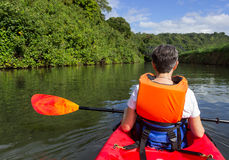 Senior lady in canoe approaching Hanalei bridge Stock Photo