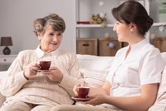 Senior lady with caregiver. Photo of senior lady with positive caregiver talking Stock Photography