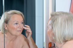 Senior lady checking her skin in the mirror Stock Photography