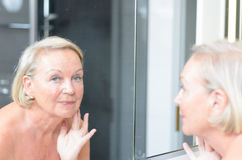 Senior lady checking her skin in the mirror Stock Images