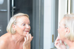 Senior lady checking her skin in the mirror Royalty Free Stock Photography
