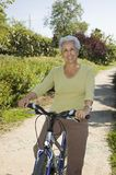 Senior lady ciclying. Senior lady on her bicycle in the park Royalty Free Stock Image