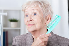 Senior lady combing hair Royalty Free Stock Images