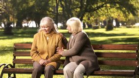 Senior lady comforting old friend about her loss, sitting on bench in park. Stock photo royalty free stock photos