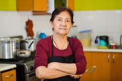 Senior lady cook from home holding a wooden spoon stock photography