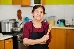 Senior lady cook from home holding a wooden spoon stock photos