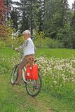 Senior lady cyclist. Senior lady on a bicycle with her dachshund puppy. Also available in horizontal Stock Photos