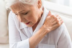 Senior lady is demonstrating suffering from ache stock photos