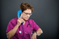 Senior lady doctor talking at telephone looking at wrist watch. Like being late on black background with copyspace advertising, area Royalty Free Stock Image