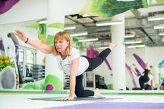 Senior lady is doing yoga. In gym, workout for mind and body royalty free stock photography