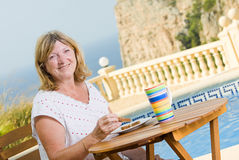 Senior Lady Eating Her Breakfast Poolside Royalty Free Stock Photography