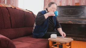 Senior lady - elderly woman at home drinking from a mug - pension life Stock Photo