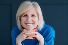 Senior lady emotion delight happiness face hands. Senior lady portrait. Emotion and facial expression. Delight and happiness. Face on hands. Toothy smile. Blue royalty free stock image