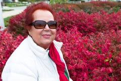 Senior Lady Enjoying the Burning Bushes Stock Photos