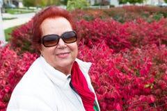 Senior Lady Enjoying the Burning Bushes Stock Images