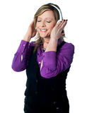 Senior lady enjoying music, lost deeply in it Royalty Free Stock Photography