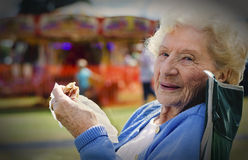 Senior Lady Enjoying Picnic at Funfair Royalty Free Stock Images