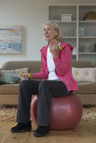 Senior lady exercising at home. Senior lady sitting on a gym ball in her home whilst using dumbbells Royalty Free Stock Photos